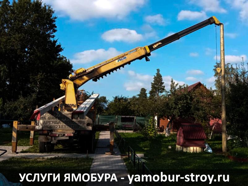 Ямобур устанавливает столб